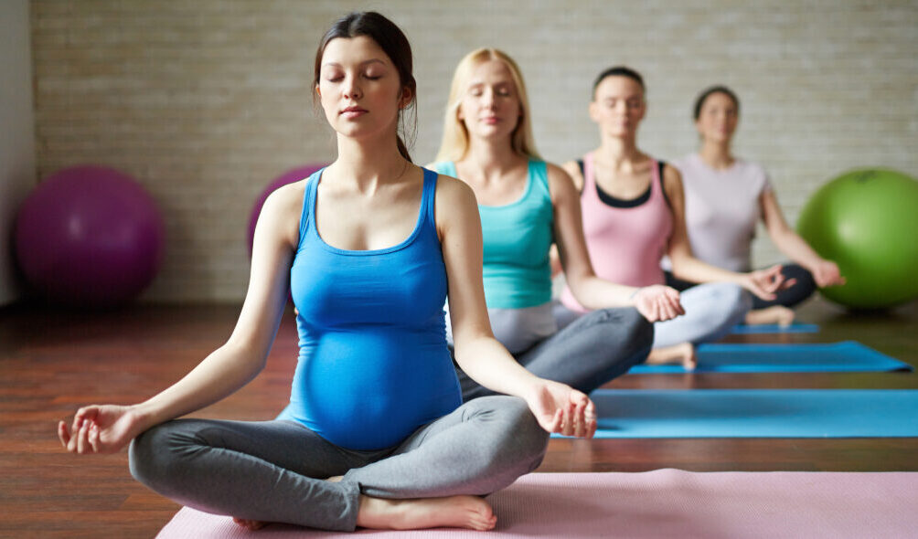Group of future mothers practicing yoga exercises